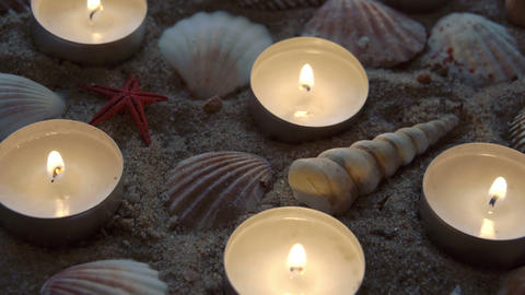 Six candles and some seashells on the sand Footage