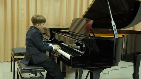 Boy playing the grand piano 画像