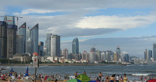4k many people at crowded sandy beach.People swimming in sea,QingDao,China Footage