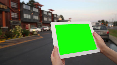 A woman holds a blank tablet PC with a green scree Footage