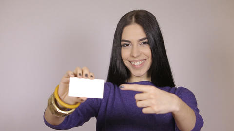 Friendly woman holding a business card and smiling Footage