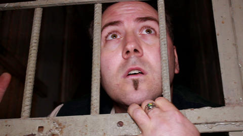 Frightened Man Behind Bars stock footage