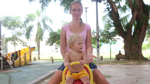 baby sitting on a yellow rocking Footage