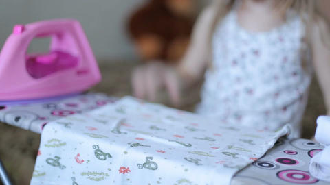 Little girl is ironing clothes Footage