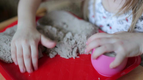 Little girl sculpts figures out of the sand Footage