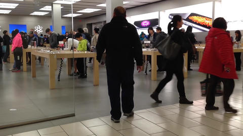 One side of people shopping in Apple store in Burn Footage