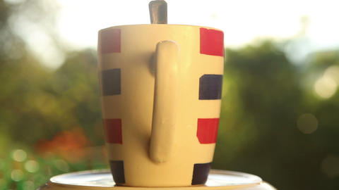 Striped Cup With Coffee On Rotated Plate stock footage