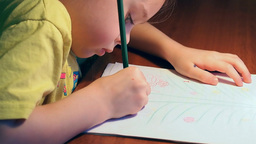 Little girl draws with concentration at the ta Footage