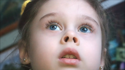 Face of a cute little girl watching TV with intere Footage
