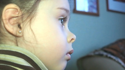 Cute little girl watching TV with great intere Footage