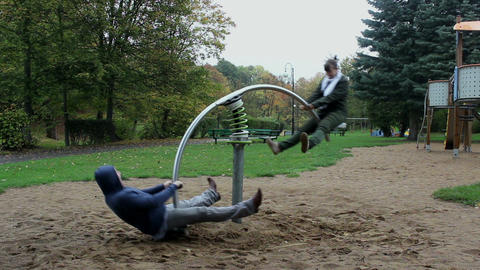 Two adults have fun on the seesaw springer - timel Stock Video Footage