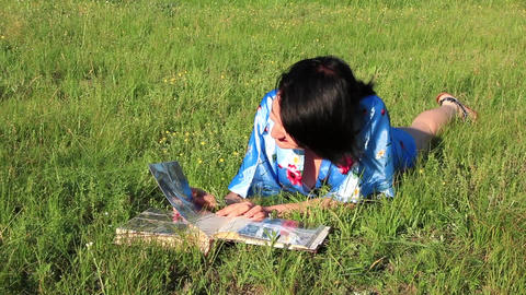 Girl with photo album on the grass Footage