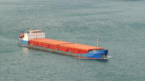 Cargo ship cruising into open sea. Aerial View Footage