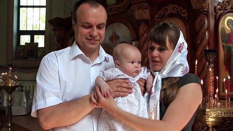 Mother and father with baby in orthodox church after christening ceremony Footage