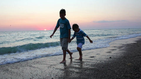 Children walking on the beach at sunset Stock Video Footage