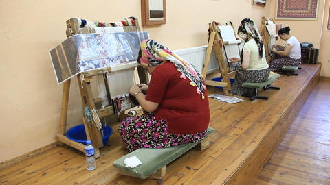 Carpet weaving. Turk woman making a silk carpet Footage
