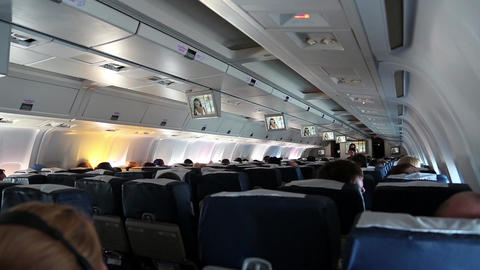 People Watching A Movie Aboard An Airplane Boeing 767 stock footage