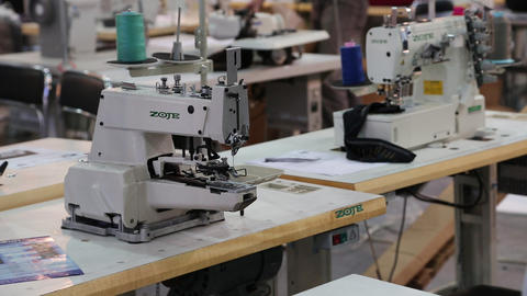 Workers and stitching machines at clothing factory Footage
