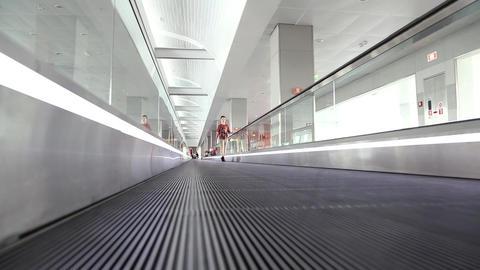 Boy on travelator inside waiting space in international airport Footage