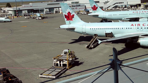 Air Canada airplanes sit parked at terminal of air Footage