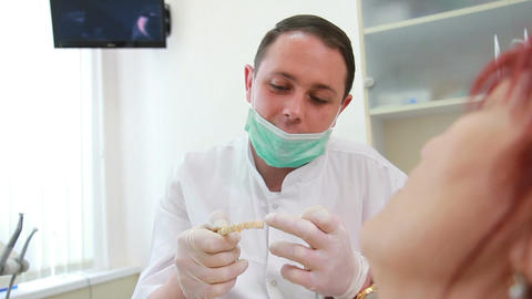 therapeutic dentistry - the dentist talks to a patient about the cast of the jaw Live Action