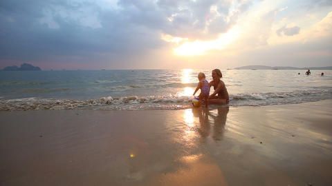 child play with mom on the beach at sunset Footage