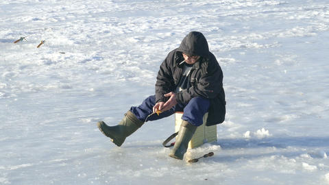 Fisherman catches with a cigarette in winter under Stock Video Footage
