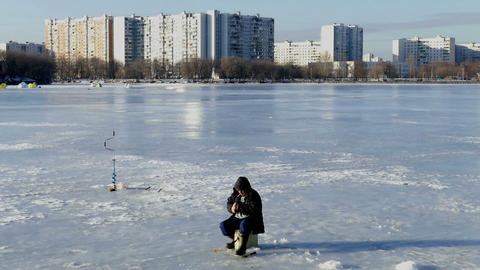 Fisherman Catches With A Cigarette In Winter Under stock footage