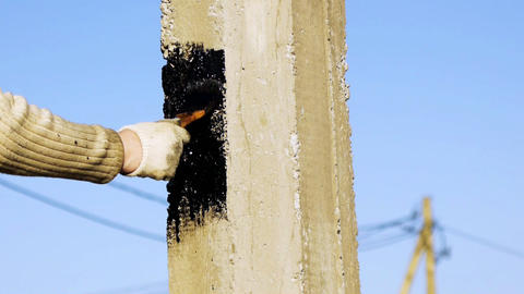 Water-proofing a pile with bitumen (tar) mastic Stock Video Footage
