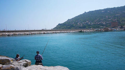 Two senior men fishing on sea shore, Alanya, Turke Stock Video Footage