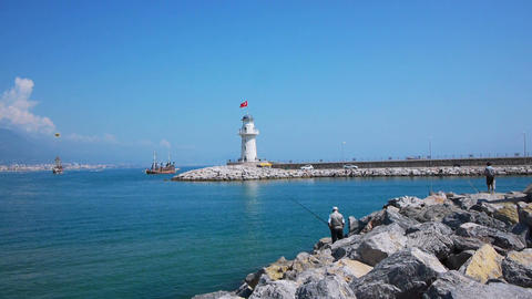 Senior men fishing in Alanya bay near lighthouse Footage