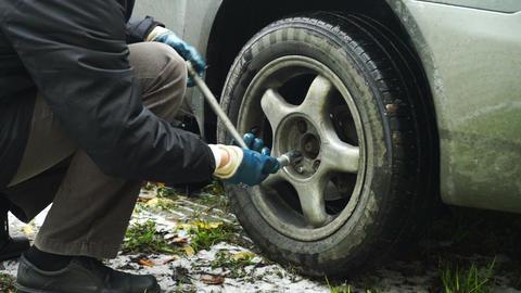 Man turning off screws from car rear wheel Stock Video Footage