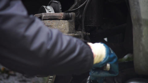 Man taking off brake caliper Stock Video Footage