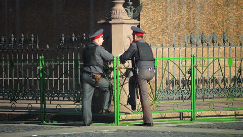Two policemen chatting near green fence, Saint Pet Footage