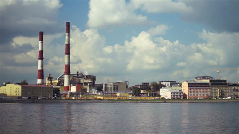 Large factory with chimney-stalks on city quay Footage