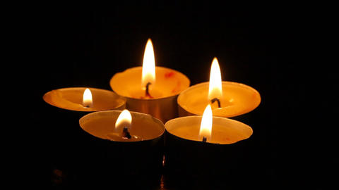 Five small burning candles against a dark backgrou Footage