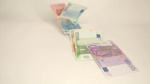 Few Euro bills dropping off the table Live Action