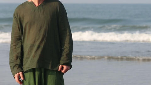 guy looking around on seashore at the waves backgr Footage