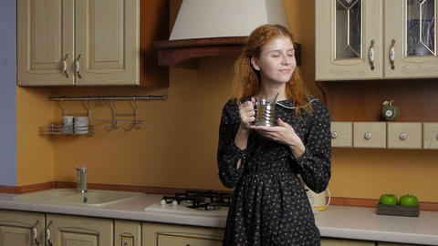 Girl drinking tea in the kitchen and dreams Footage
