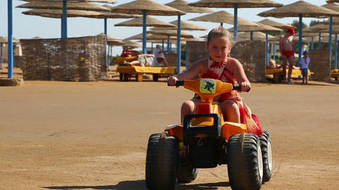 Little girl riding a toy car on the beach Footage