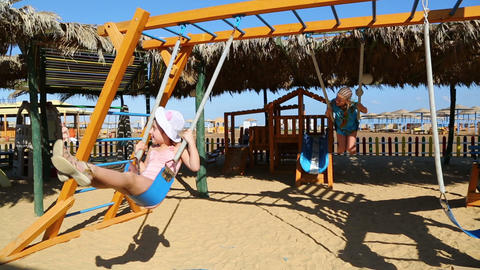 two little girls swinging on a swing at the beach Footage
