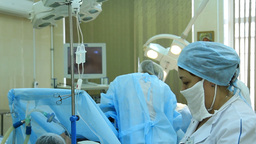 Oncosurgery: Medical personnel adjusts a dropper during surgery Footage