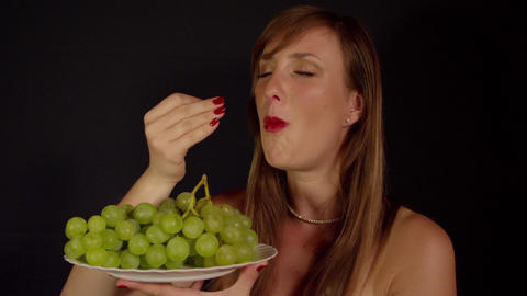 Young woman eating green grapes Footage