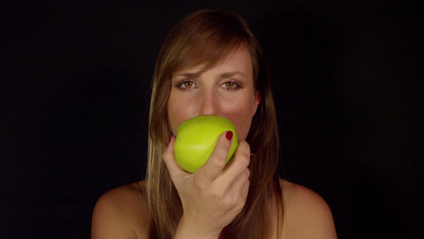 Young woman takes a bite of an apple Footage