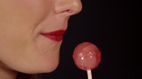 SLOW MOTION CLOSE UP: Woman licking lollipop Footage