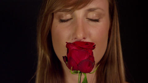 Young woman smells red rose and smiles Live Action