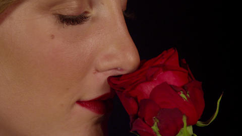 CLOSE UP: Smiling woman smelling red rose Footage