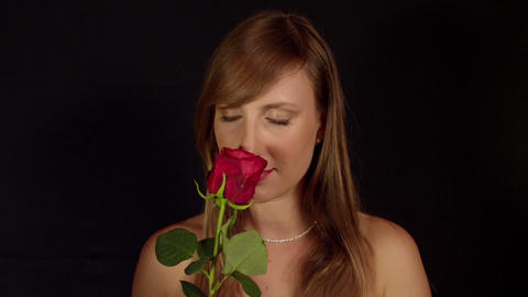 Topless woman smelling red rose Live Action