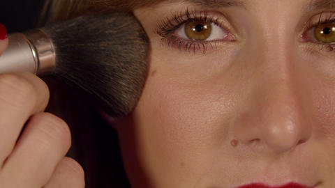 SLOW MOTION CLOSE UP: Woman applying bronzer to he Footage