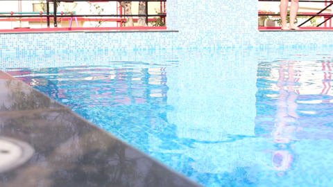 girl standing at edge of hotel pool among planting Footage